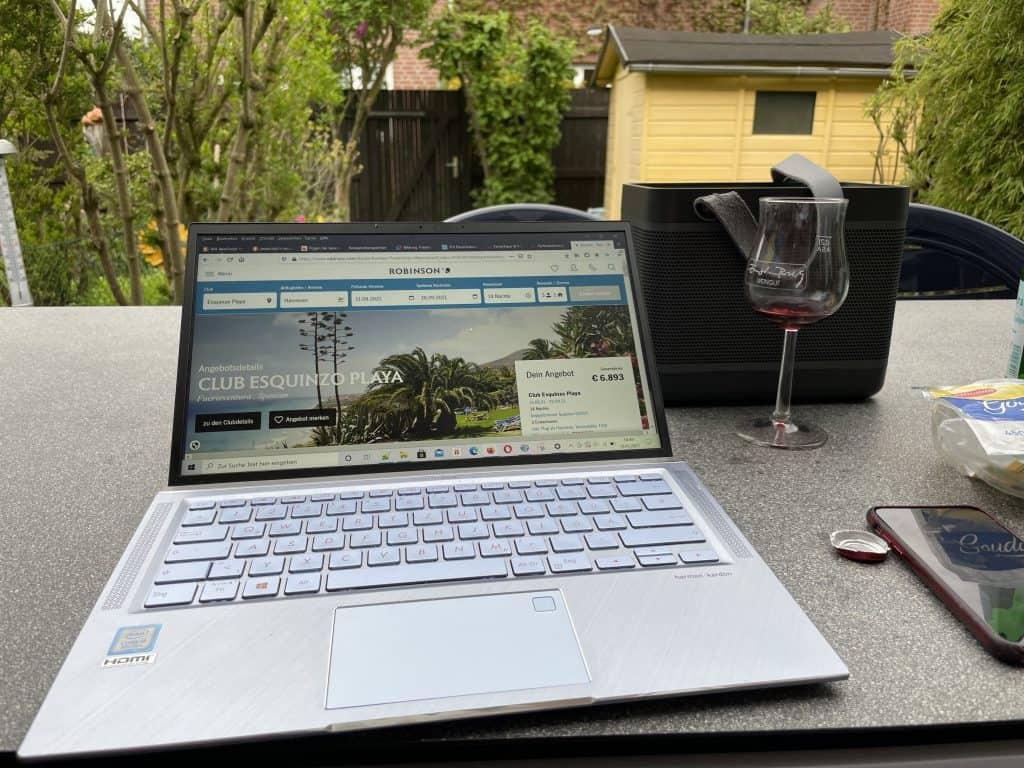 Notebook mit Urlaubsseite auf Gartentisch