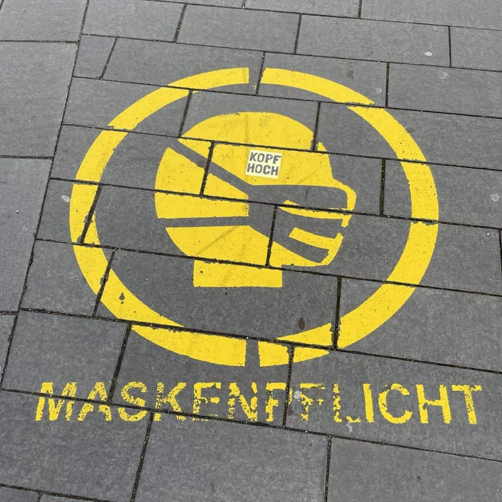 Maskenpflichtsymbol auf den Fußweg gesprüht